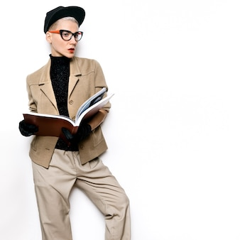 Vintage fashion girl student beige classic jacket and stylish accessories. red lipstick, retro glasses. gloves. red book. love vintage outfit
