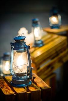 Vintage fashioned rustic kerosene oil lantern lamp burning with a soft glow warm light