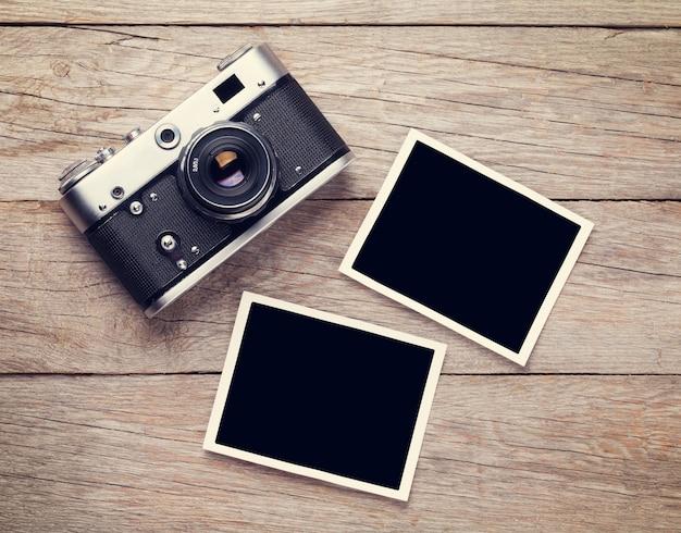 빈티지 필름 카메라와 나무 테이블에 두 개의 빈 사진 프레임. 평면도