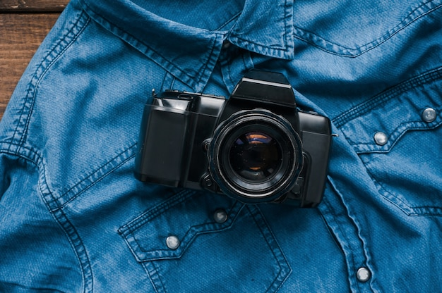 Vintage film camera on denim shirt