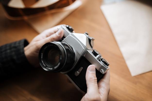 男のビンテージフィルムカメラは木製の空間に手します。