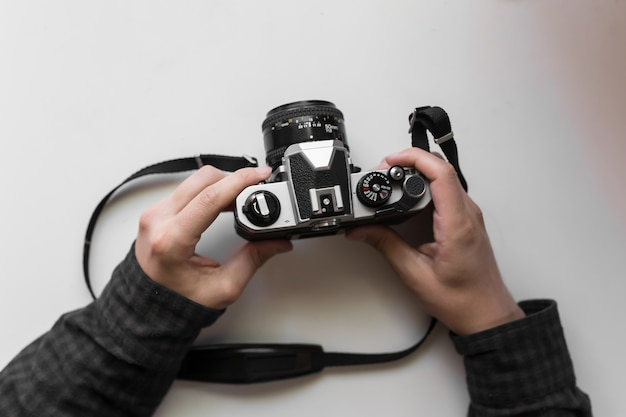 Vintage film camera in the man hands on a white space