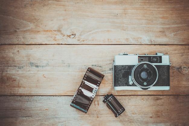 古い木製の背景にヴィンテージフィルムカメラ。