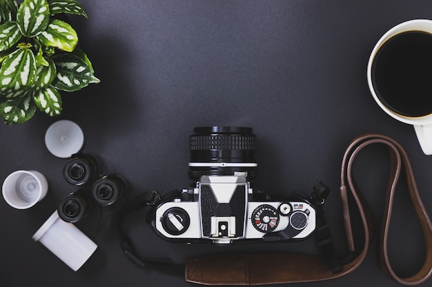Vintage film cameras and film rolls, black coffee, trees placed on a black background