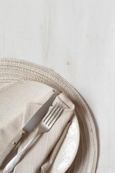 古い木製のテーブルの上の皿にビンテージフォークとナイフ