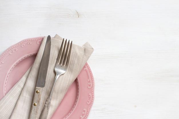 プレート表面にナプキンが付いているビンテージフォークとナイフ