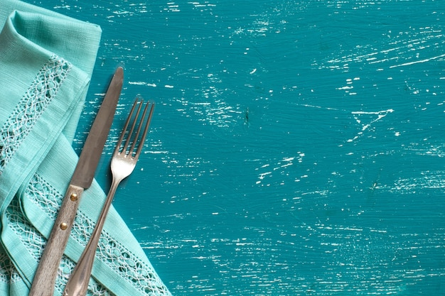 Vintage fork and knife on napkin on a turquoise wood