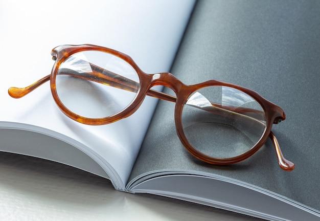 空白のページで開いた本の上に横たわっているヴィンテージメガネ