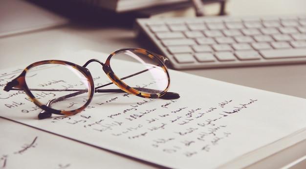 Vintage glasses, notebook and keyboard