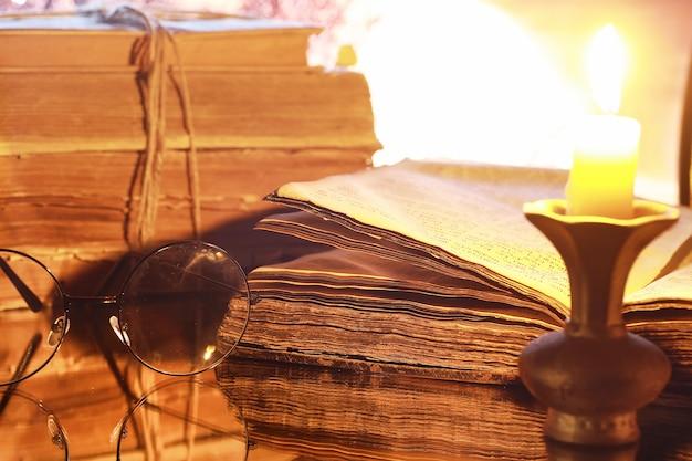 月の背景に古いレトロな本のヴィンテージメガネ。ろうそくの明かりで本を読む。本のスリラーと小説の概念。