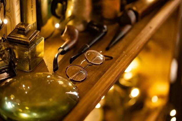 虫眼鏡、喫煙パイプ、レトロなものが付いたワードローブの棚に丸いフレームが付いたヴィンテージグラス。骨董品の収集。弱い光。セレクティブフォーカス。