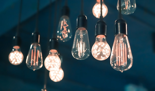 Vintage glowing filament light bulb lamps hanging on the wall with retor blue color backgr