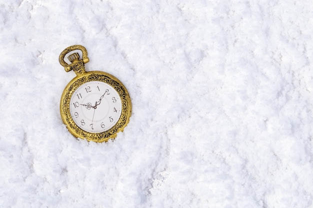 Vintage gold clock (pocket watch) on snow. top view.