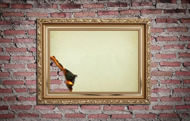 Старинная золотая рамка с сожженным на фоне стены