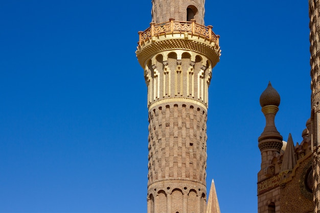 Vintage golden minaret on bright blue sky close-up.