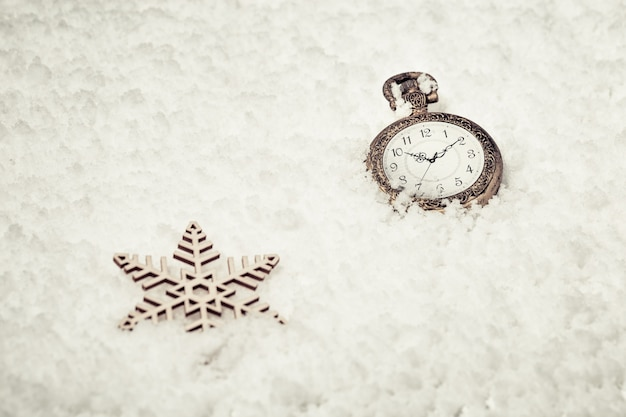 Vintage golden pocket watch  and toy snowflakes on snow