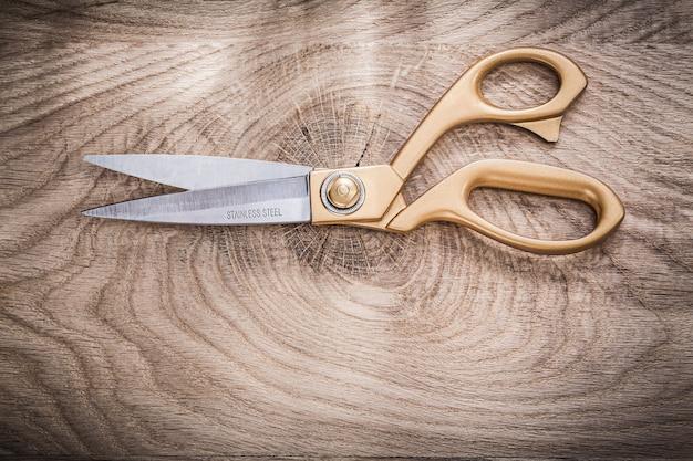 Vintage golden scissors on wooden board