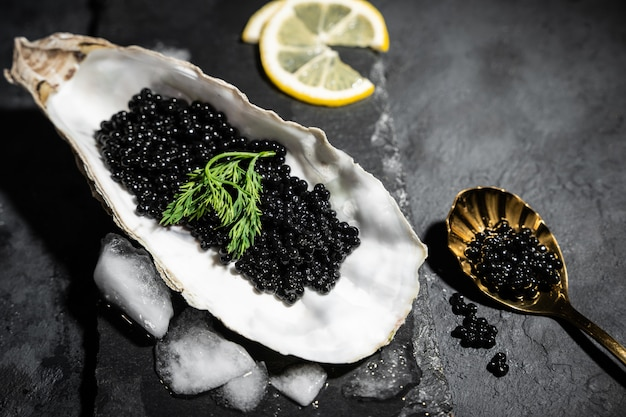 Vintage golden spoon with black sturgeon caviar and oyster on black slate stone table. copy space