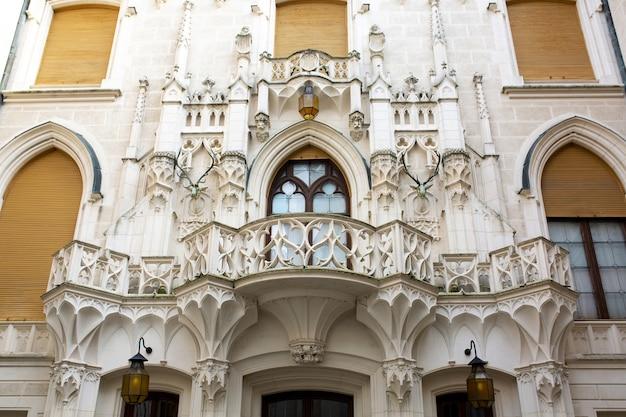 プラハの古代の城の美しいファサードにある木製のシャッター付きのヴィンテージのゴシック様式の窓
