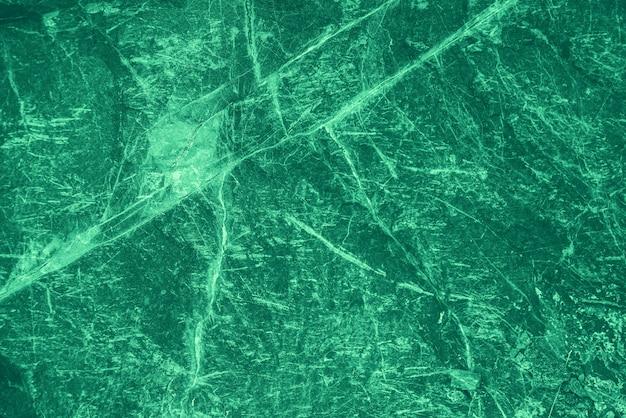 ヴィンテージの緑の背景。エメラルド色の粗く塗られた壁。鮮やかな色の不完全な平面。緑の色合いの不均一な古い装飾的なトーンの背景。エメラルド色相のテクスチャ。装飾的な石の表面。