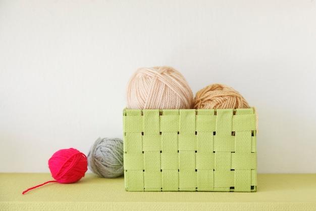 다른 색상의 모직 공이 가득한 빈티지 녹색 상자
