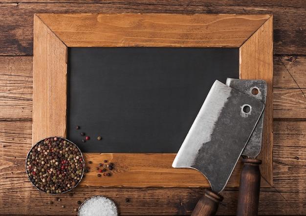 木製の背景に塩とコショウのメニュー表示板と肉のヴィンテージ手斧。