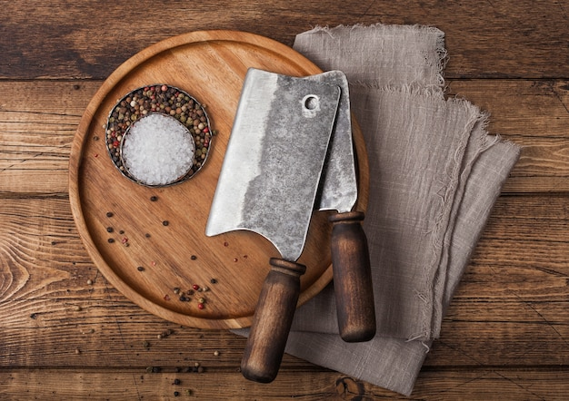 Vintage hatchets for meat on round wooden plate with salt and pepper on wooden background with linen towel.