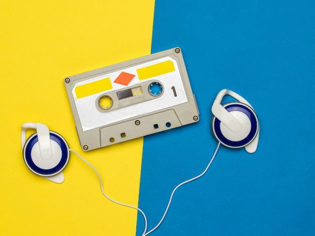 노란색과 파란색에 자기 테이프와 빈티지 헤드폰 및 오디오 카세트. 빈티지 오디오 녹음 저장 및 재생 도구.