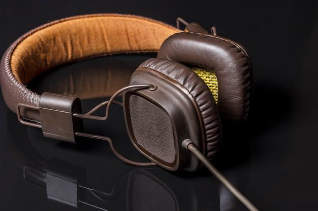 反射のある黒い表面の音楽用のビンテージヘッドフォン