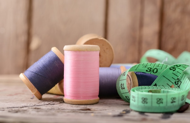 Vintage hipster multicolor threads bobbins old wooden table. atelier, sewing accessories