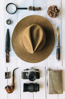Vintage hipster travel or hiking accessories flat lay with hat and camera