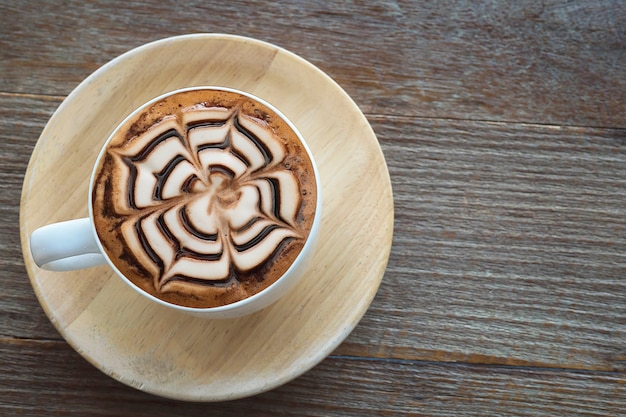 Vintage hot coffee cup with nice latte art decoration on old wooden texture table