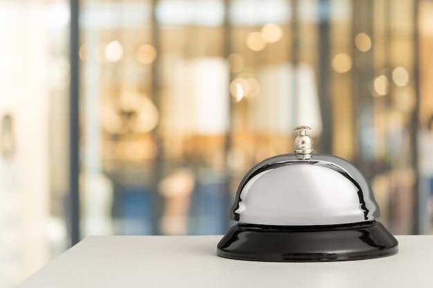 Винтажный звонок на стойке регистрации отеля на размытом фоне, боке