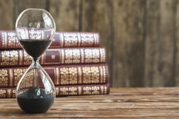 오래 된 책의 스택에 대 한 빈티지 모래 시계