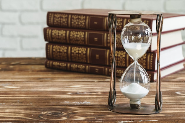 Vintage hourglass against a stack of old books close up