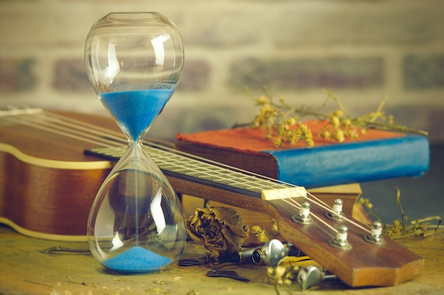 A vintage hourglass and ukulele with an old book and brass pen on a wooden table
