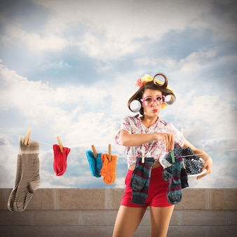 カーラー付きのヴィンテージ主婦が洗濯物を伸ばす