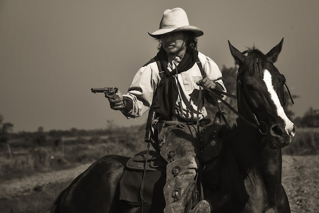 Vintage image of cowboy showing horse riding, and shooting guns