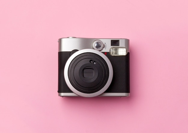 Vintage instant camera at pastel pink table.
