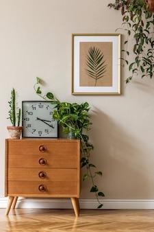 베이지 색 벽에 디자인 복고풍 나무 옷장, 식물, 선인장, 검은 색 시계 및 골드 프레임이있는 거실의 빈티지 인테리어 디자인. 세련된 가정 장식. 최소한의 개념.