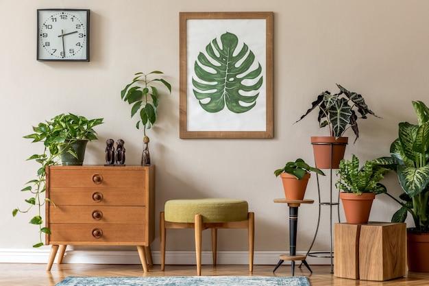 Винтажный дизайн интерьера гостиной со стильной ретро-мебелью, множеством растений, комодом, черными часами и коричневым постером - макет рамки на бежевой стене. стильный домашний декор. шаблон.