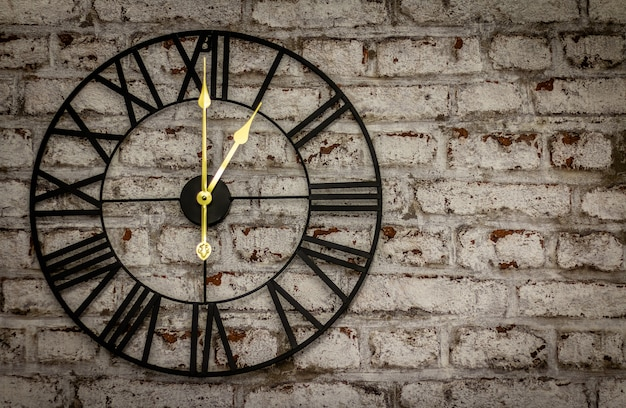 Vintage iron clock on brick wall with golden hands