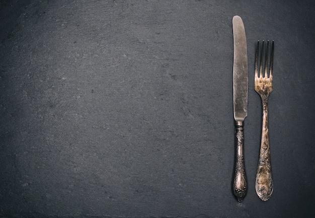 Vintage iron fork and knife on black