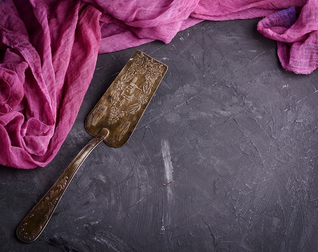 Vintage iron spatula for dessert on a black surface