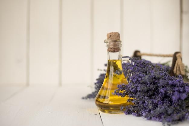 フランスのプロヴァンスのフィールドブーケの上に芳香のあるラベンダーオイルが入ったヴィンテージの瓶。