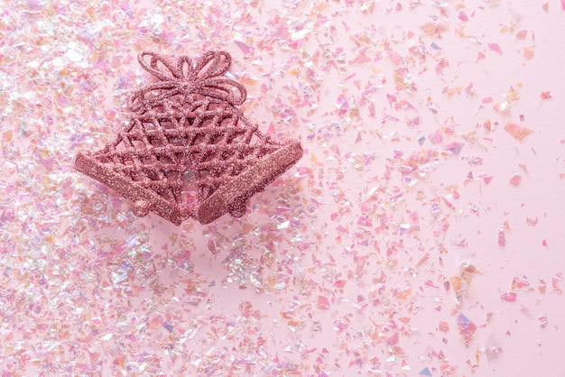 Vintage jingle bell on pink glitter . minimal christmas . happy new year. flat lay, top view, copyspace
