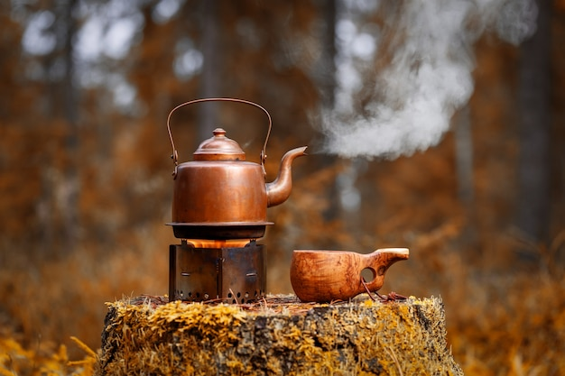 Vintage kettle with coffee on the stove and a wooden cup on an old stump in forest