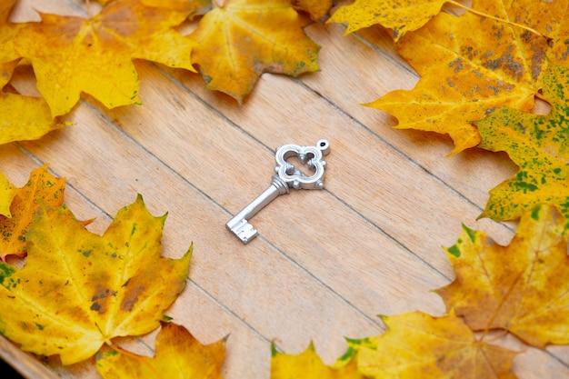 ヴィンテージの鍵とカエデの葉が木製のテーブルに