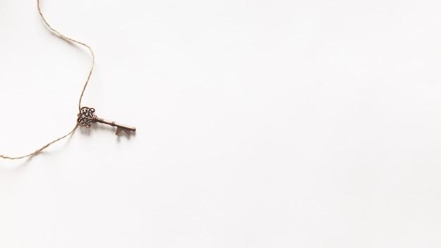Vintage key hanging on white background