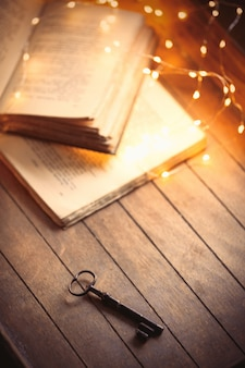 Vintage key and old books on wooden table